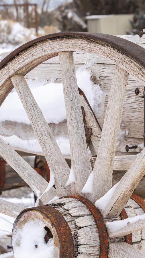 Cierre vertical claro para arriba de la rueda de un carro de madera viejo contra un paisaje nevoso en invierno fotos de archivo