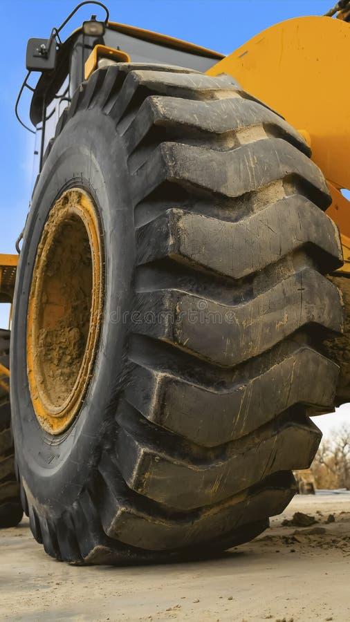Cierre vertical del marco encima de la vista de los neumáticos de goma negros enormes de un vehículo amarillo de la construcción fotos de archivo