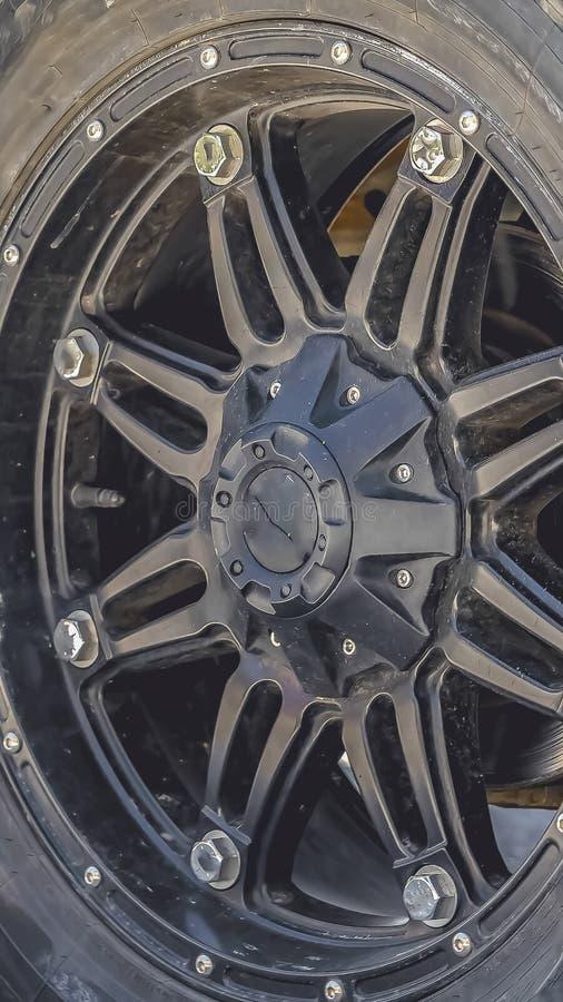 Cierre vertical encima de la vista de la rueda de goma negra de un vehículo parqueado en un camino iluminado por el sol imágenes de archivo libres de regalías