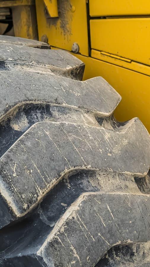 Cierre vertical para arriba del neumático de goma negro de un vehículo de la construcción con la pintura amarilla fotos de archivo libres de regalías