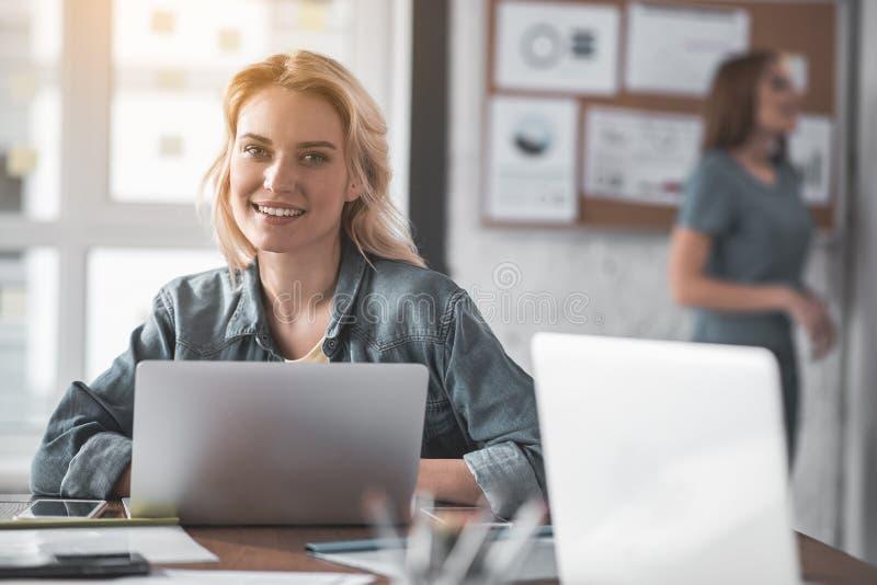 Ciesząca się dama przy jej pracującym miejscem fotografia stock