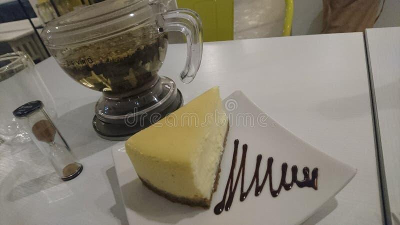 Cieszyć się ładnego kawałka cheesecake z ziołową herbatą zdjęcia stock