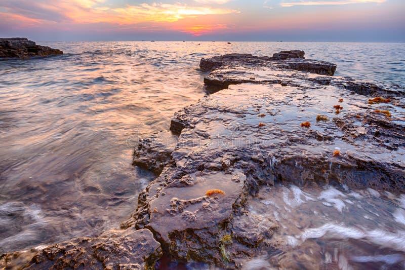 Cieszyć się kolorowego zmierzch na plaży z skałami na Adriat obraz stock