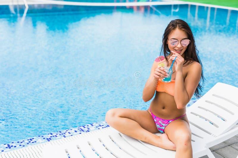 cieszyć się lato Piękna młoda kobieta pije koktajl w błękitnym seksownym bikini podczas gdy relaksujący w pokładu plażowym krześl zdjęcia royalty free