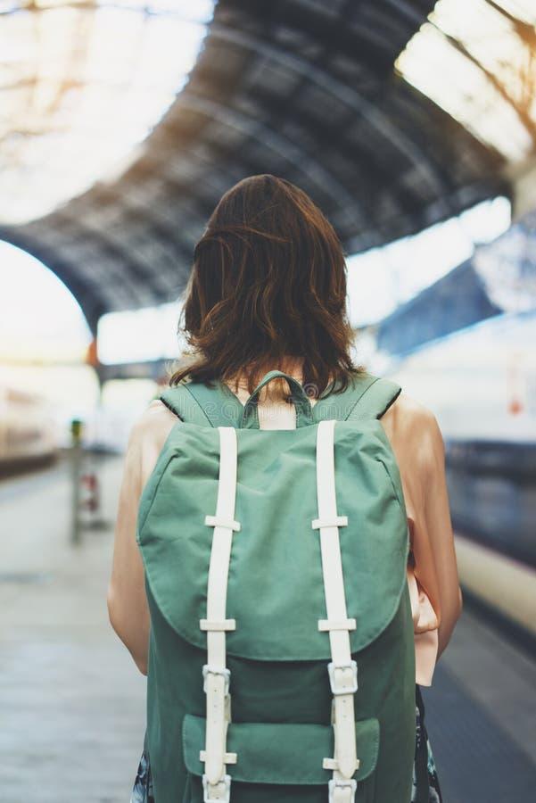 Cieszyć się podróż Młodej kobiety czekanie na stacyjnej platformie z plecakiem na tło elektrycznym pociągu Turystyczna plan trasa fotografia royalty free