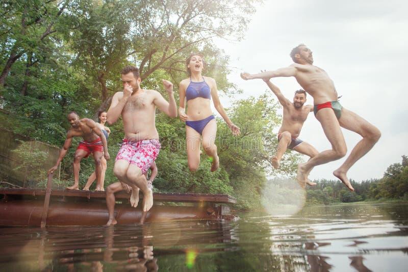 Cieszyć się rzeki przyjęcia z przyjaciółmi Grupa piękni szczęśliwi młodzi ludzie przy rzeką wpólnie zdjęcia stock