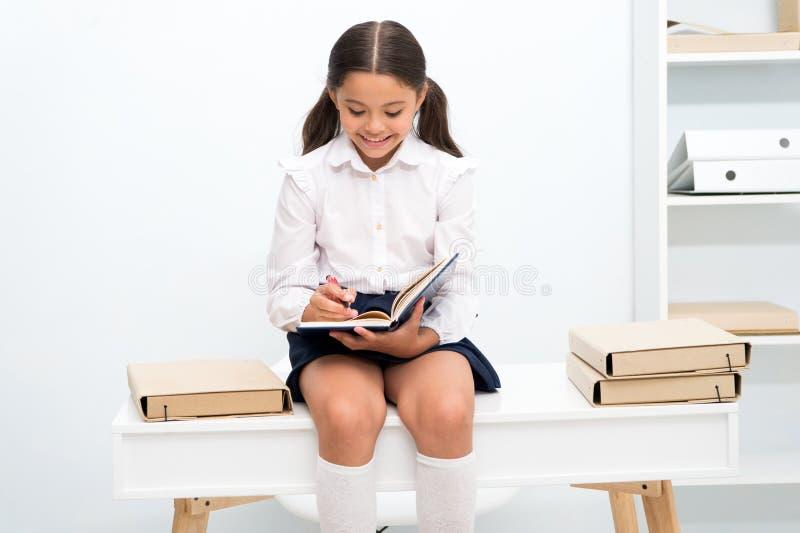 Cieszyć się studiowanie Dziewczyny dziecko czyta książkę podczas gdy siedzi na stołowym pobliskim stosie książka bielu tło Uczenn zdjęcie stock