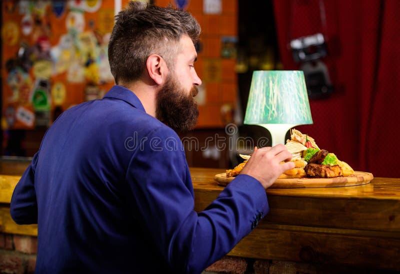 Cieszy się posiłek Restauracyjny klient Modnisia formalny kostium siedzi przy baru kontuarem Obsługuje otrzymywającego posiłek z  zdjęcie royalty free
