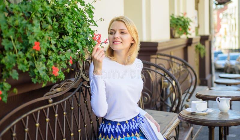 Cieszy się każdy moment twój życie Dziewczyna siedzi kawiarni obwąchuje kwiatu aromat Piękny taras przyciąga klientów Rośliny jak zdjęcia royalty free