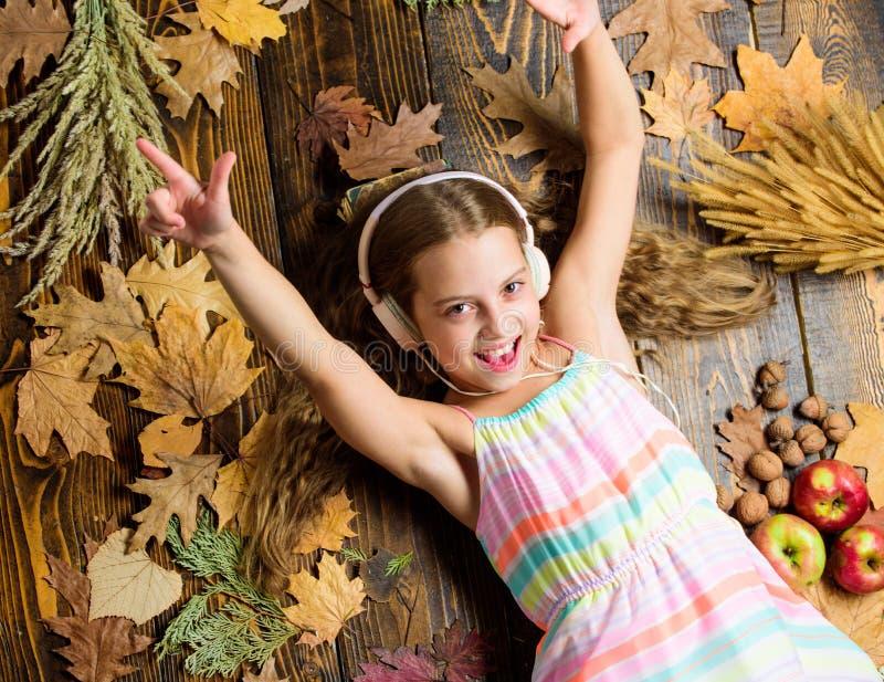 Cieszy się muzykę i relaksuje szczęśliwego dzieciństwa Dzieciak dziewczyny drewniany tło słucha muzycznych hełmofony Dziecko słuc obrazy royalty free