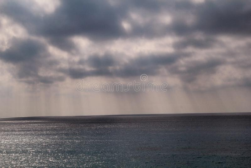 Cieux dramatiques de coucher du soleil avec les nuages gris avec des lignes du soleil vers la mer Méditerranée tropicale Bel envi image stock