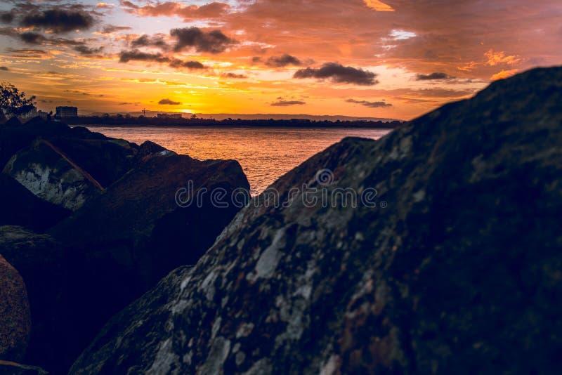 Cieux oranges sur les roches photographie stock