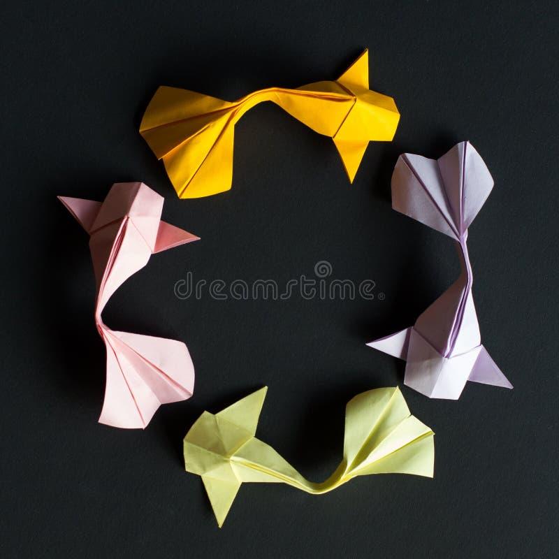 Cifra tonda circolare dei pesci fatti a mano della carpa a specchi dell'oro di origami del mestiere di carta su fondo nero Dimens immagine stock