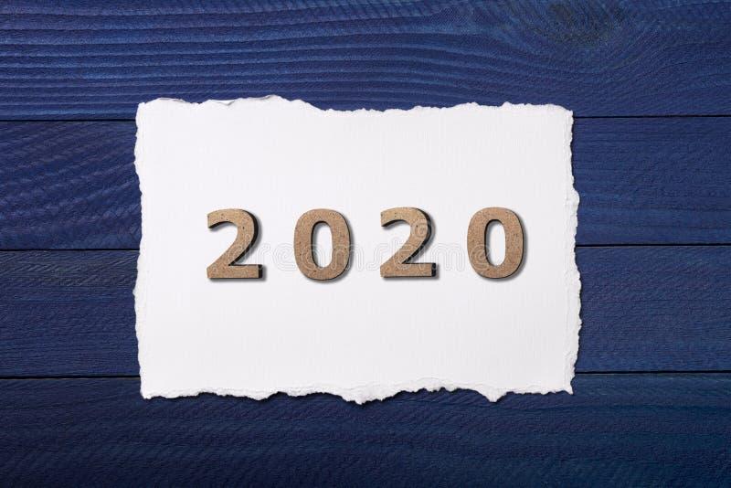 Cifre 2020 presentate su un pezzo di cartone bianco su fondo di legno blu, concetto nuovo anno, calendario immagini stock