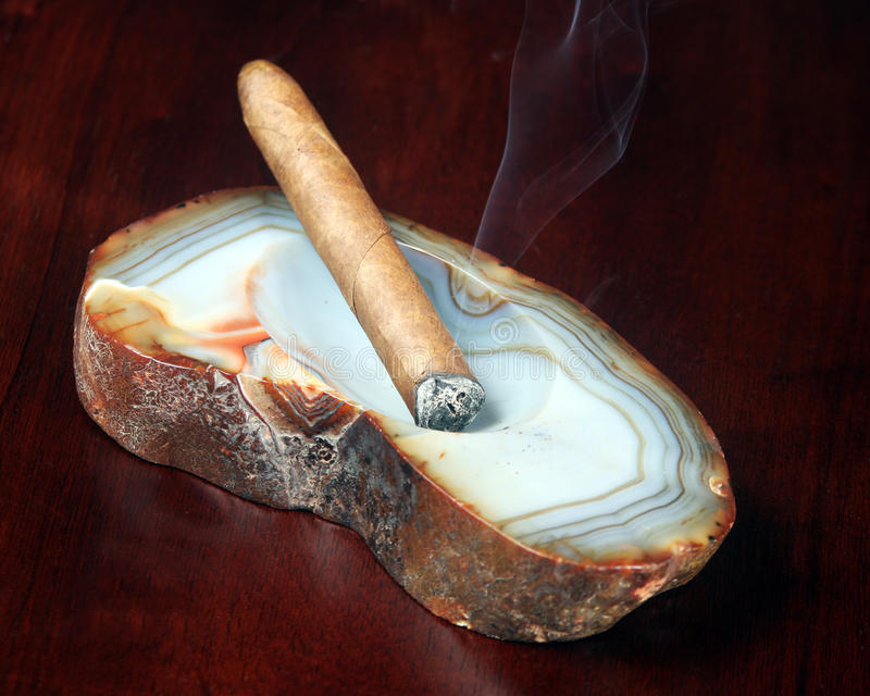 Cigar in an ashtray. Detailed closeup of a hand rolled cigar in an ashtray stock photo