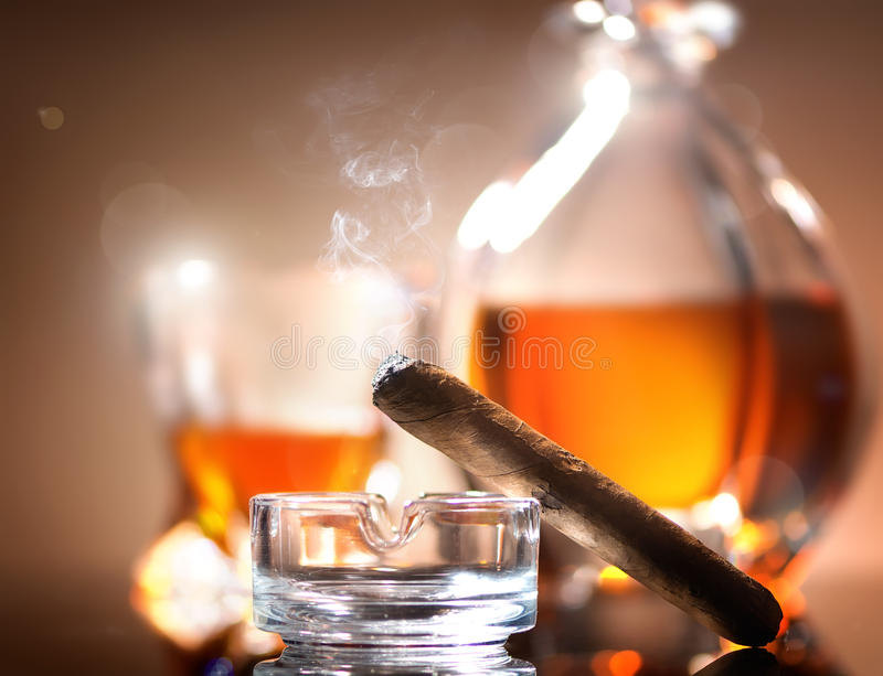 Cigar on ashtray. On a background of whiskey stock photography