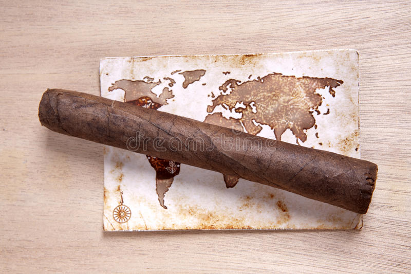 Cigar and map. Cigar lies on an ancient map stock image