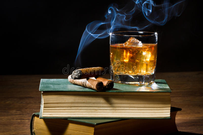 Cigar with smoke and whisky on ice and books. Cigar with blue smoke and whisky on ice and two books volume royalty free stock photo