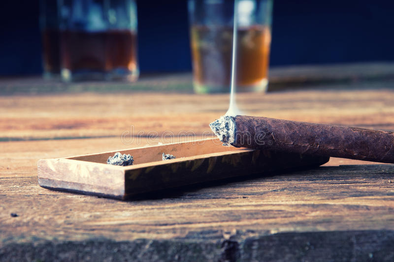 Cigar and whisky with ice on wooden table royalty free stock photos