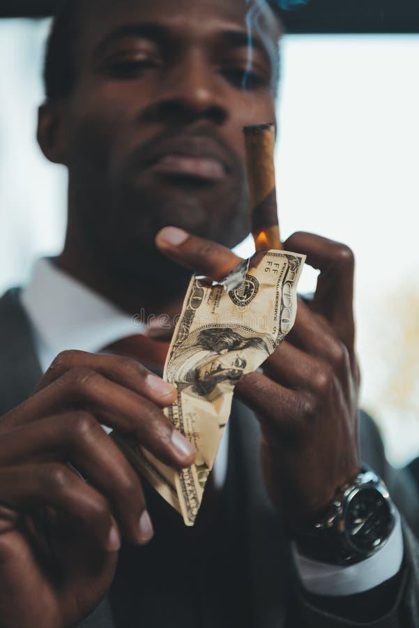 Cigare de tabagisme d'homme d'affaires d'afro-américain et billet de banque brûlant du dollar images stock