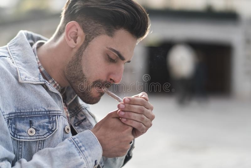 Cigare de tabagisme de jeune homme frais image libre de droits