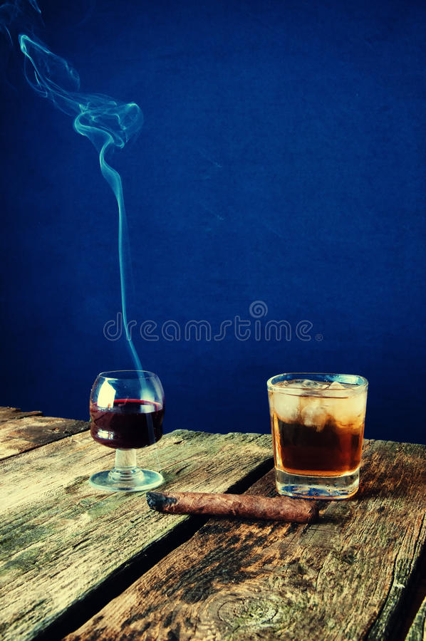 Cigare, vin et whiskey de Lit sur un fond en bois photo libre de droits