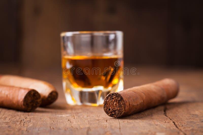 Cigares et whiskey sur la vieille table en bois photographie stock libre de droits