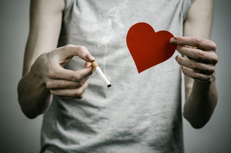 Cigarett-, böjelse- och allmän hälsaämne: rökaren rymmer cigaretten i hans hand och en röd hjärta på en mörk bakgrund i royaltyfri fotografi