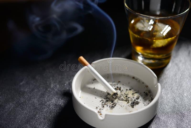 Cigarett i askfat med exponeringsglas av whisky royaltyfri fotografi