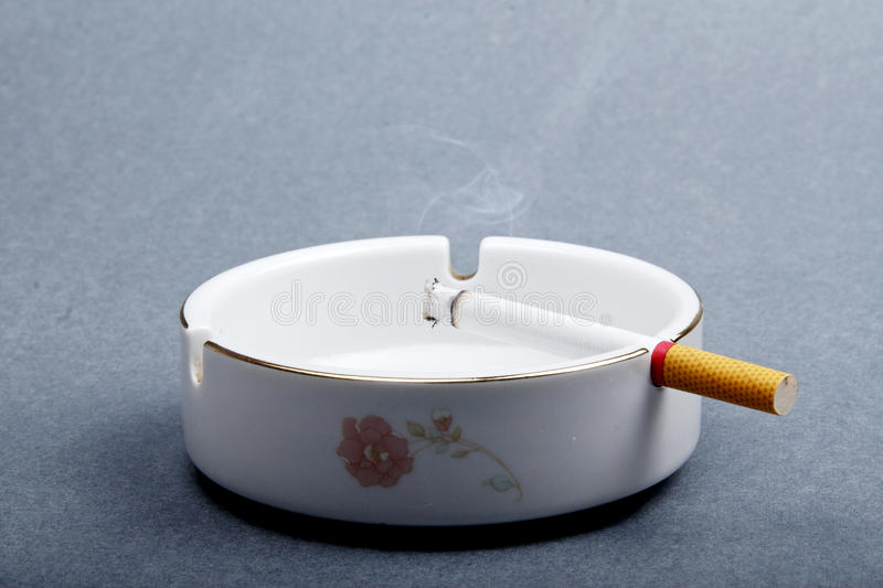 Cigarette on the ashtray. A cigarette lighted is on the ashtray royalty free stock images
