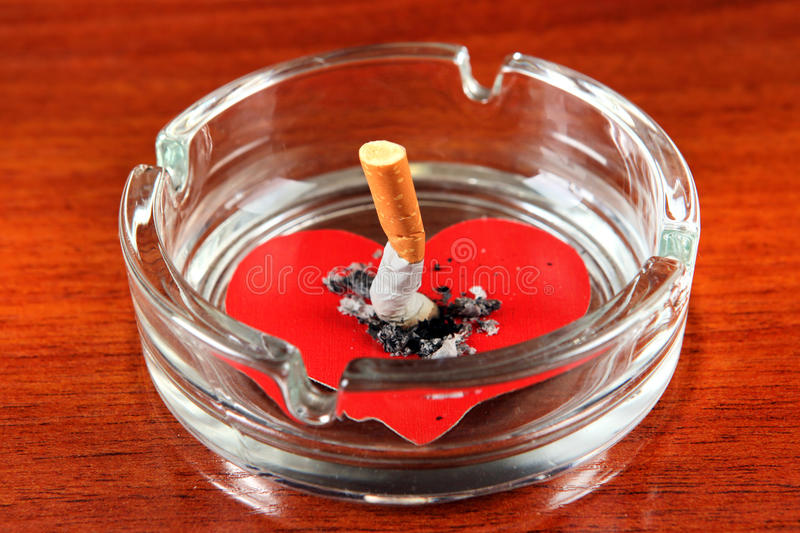 Cigarette in Ashtray. With Heart Shape on the Table stock photos