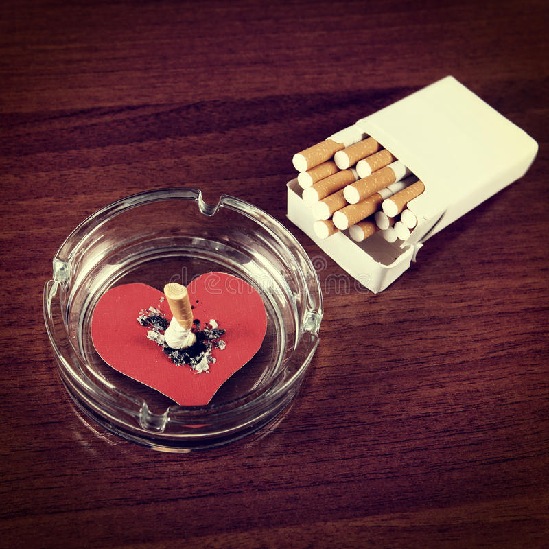 Cigarette in Ashtray. Vignetting Photo of Cigarette in Ashtray with Heart Shape on the Table stock photography