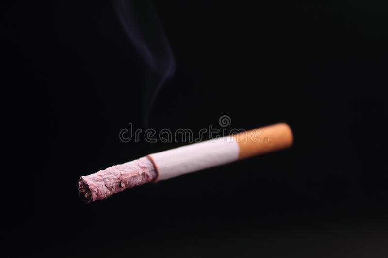 Cigarette on a black background. Cigarette as a symbol of human dependence on addictions royalty free stock photo