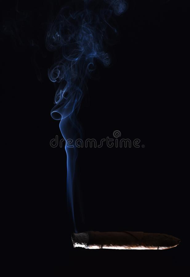 Cigarette with blue smoke on black background royalty free stock photo