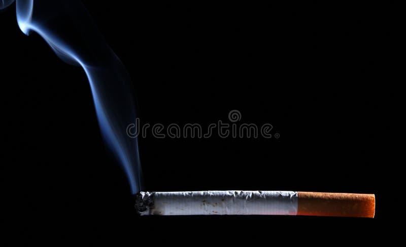 Cigarette brûlante au-dessus de fond noir avec de la fumée photographie stock libre de droits