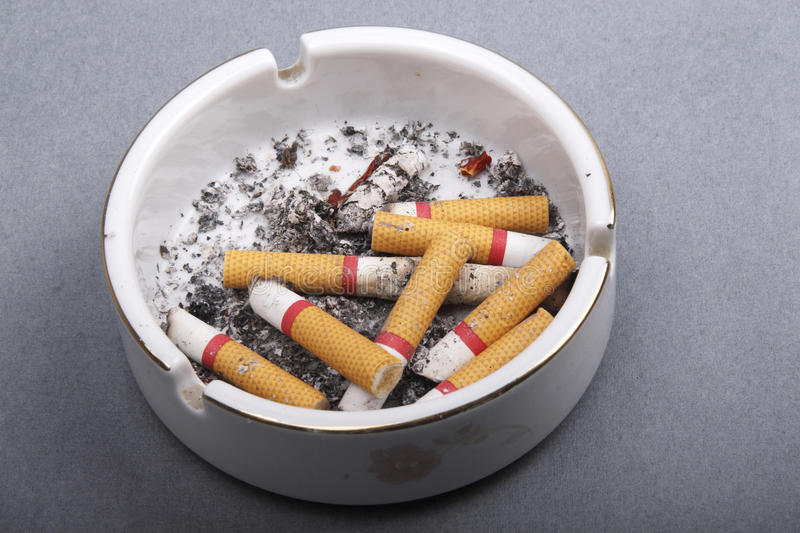 Cigarette butts in ashtray. Isolated on grey background royalty free stock photos