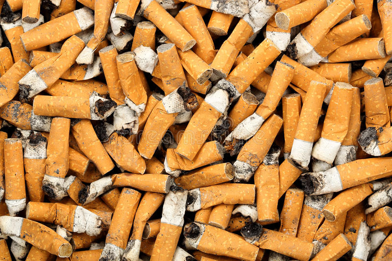 Cigarette butts. Many cigarette butts for background use stock images