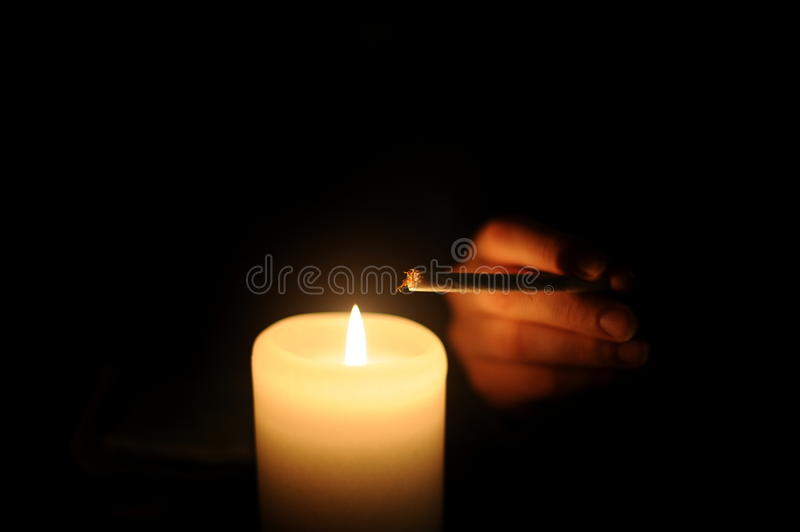 Cigarette and candle stock images