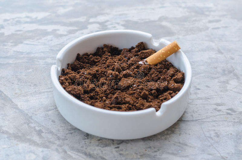 Cigarette and coffee ground on the ceramic ashtray. The ceramic ashtray contain coffee ground on concrete floor for protection fire from cigarette stock image