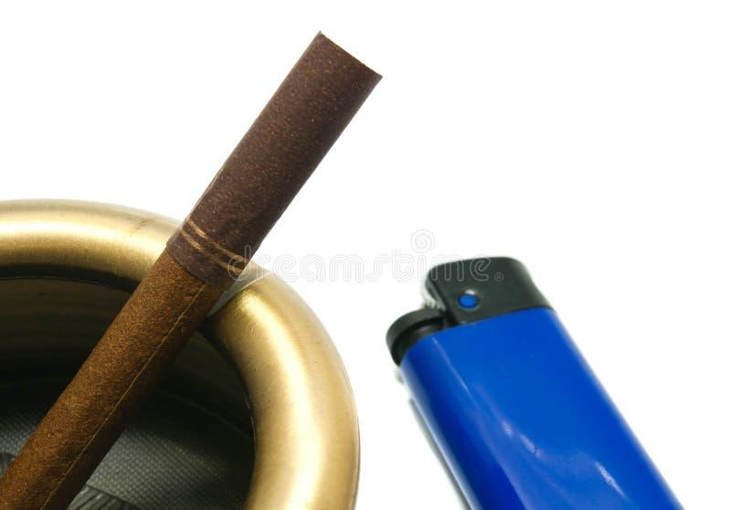 Cigarette dans le cendrier et l'allumeur bleu image stock