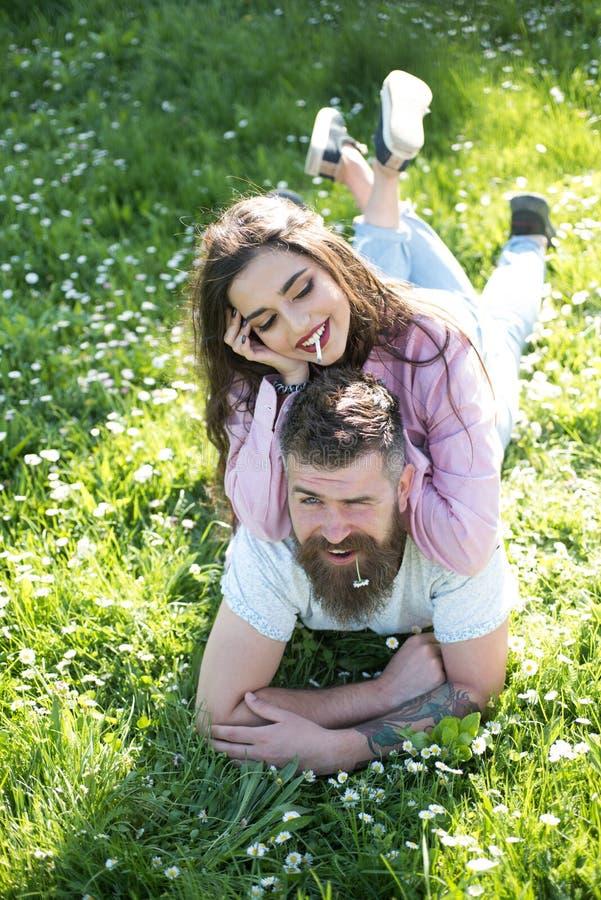 Cigarette de fumée de femme se trouvant sur l'homme avec la marguerite dans la bouche Les couples détendent sur l'herbe verte Se  photographie stock