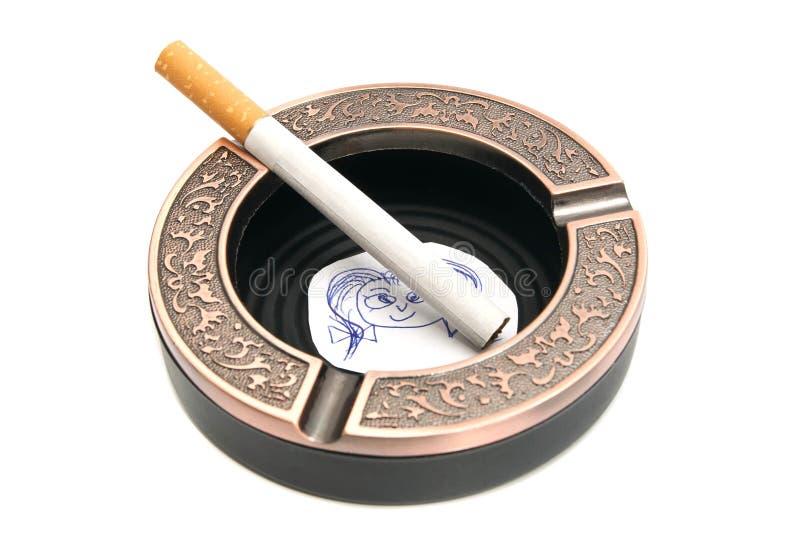 Cigarette en cendrier et portrait d'enfant photo stock