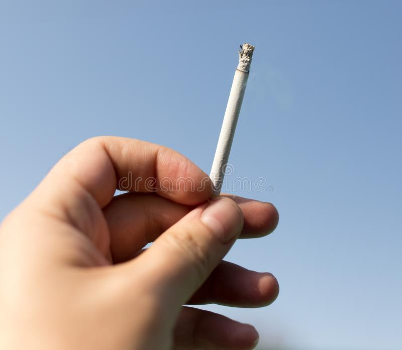 Cigarette in hand against the blue sky royalty free stock images