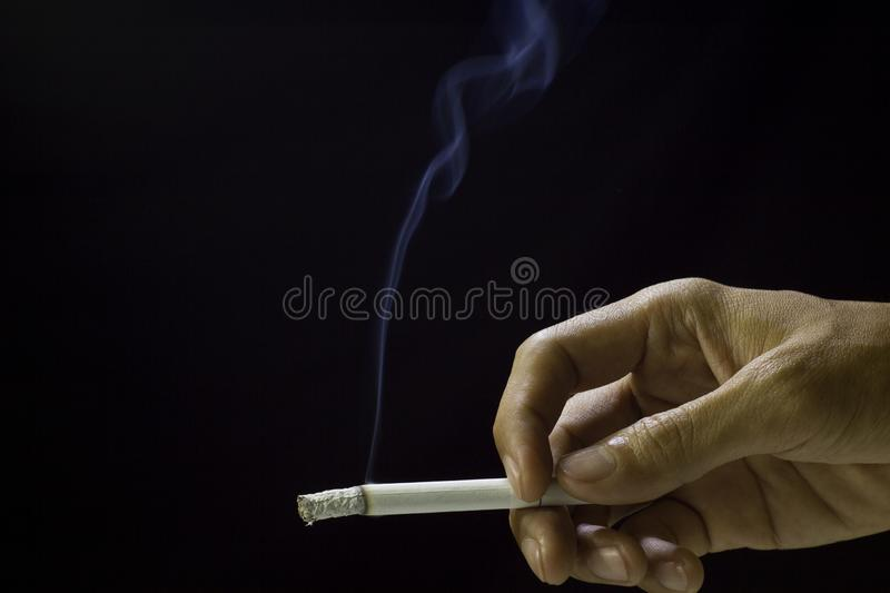 Cigarette in hand of men on black backgroundand smoke ,anti Lung cancer concept.  stock photography