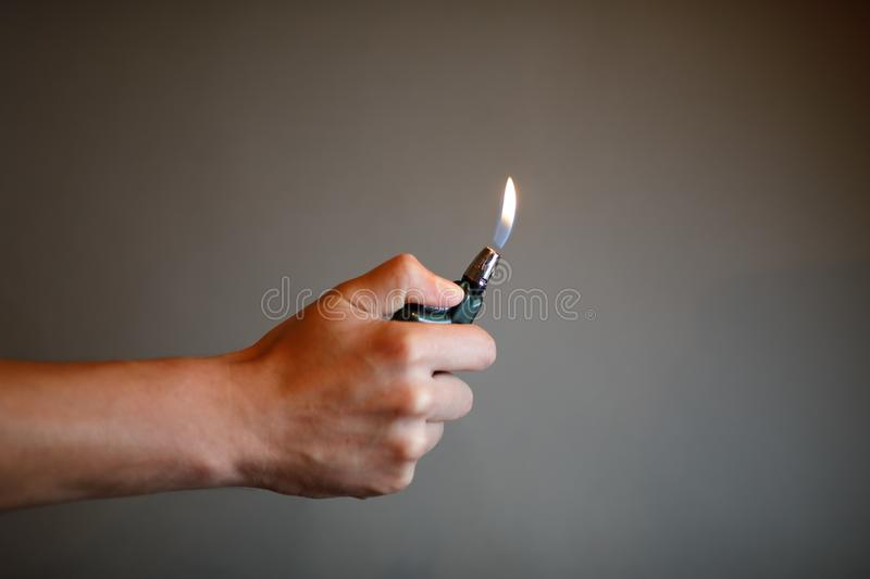 Cigarette lighter igniting by a hand stock photography