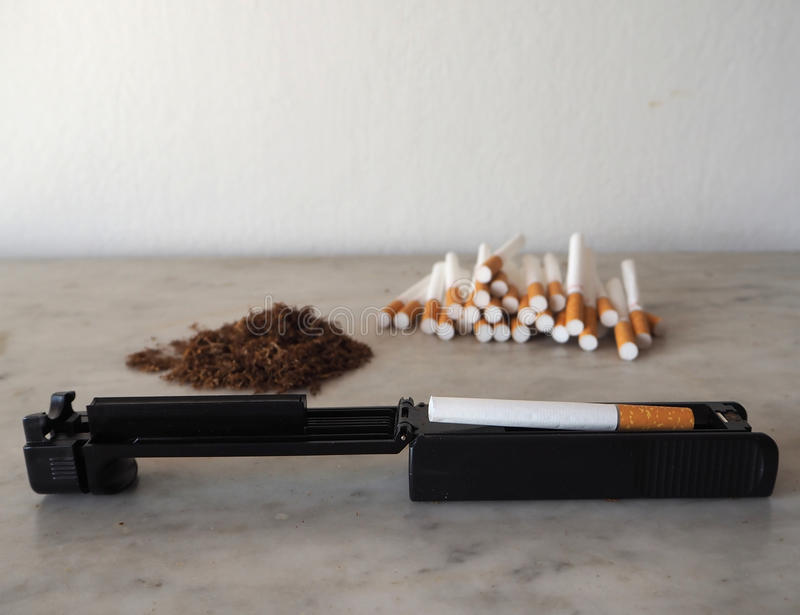 Cigarette rolling machine with empty cigarettes and tobacco on background.  stock photography