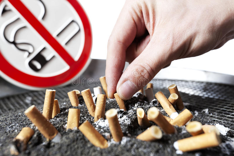 Cigarette stubs in ash and no smoking sign. royalty free stock photos