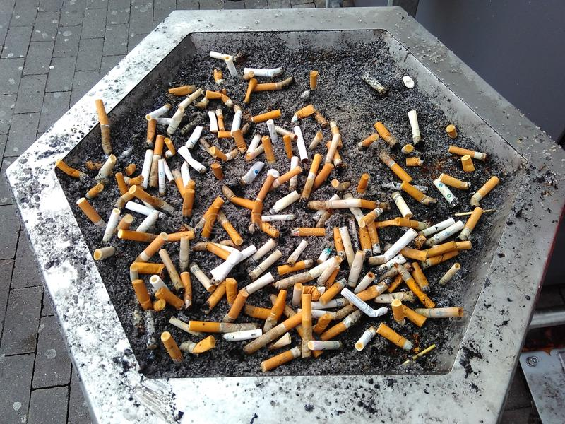 Cigarette stubs in an ashtray with sand. The problem of smoking stock photos
