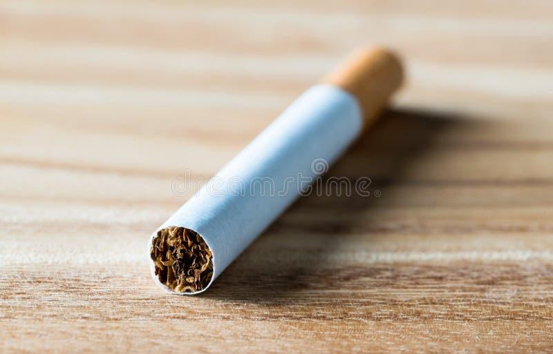 Cigarette sur la table en bois, macro fin vers le haut de vue Tabac, papier et nicotine photographie stock