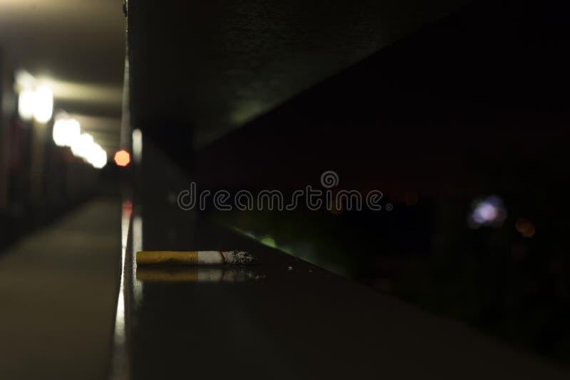 Cigarette sur le bois dans un hôtel la nuit photo libre de droits